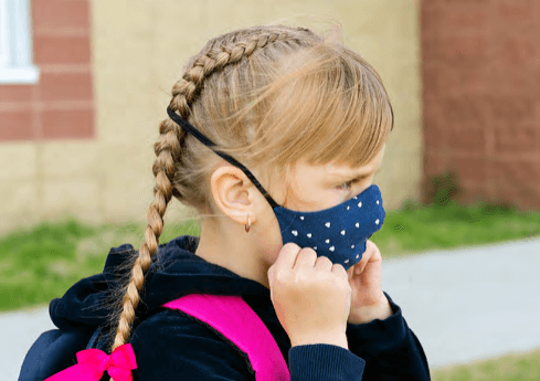 A child properly adjusting a face mask while outside of school.